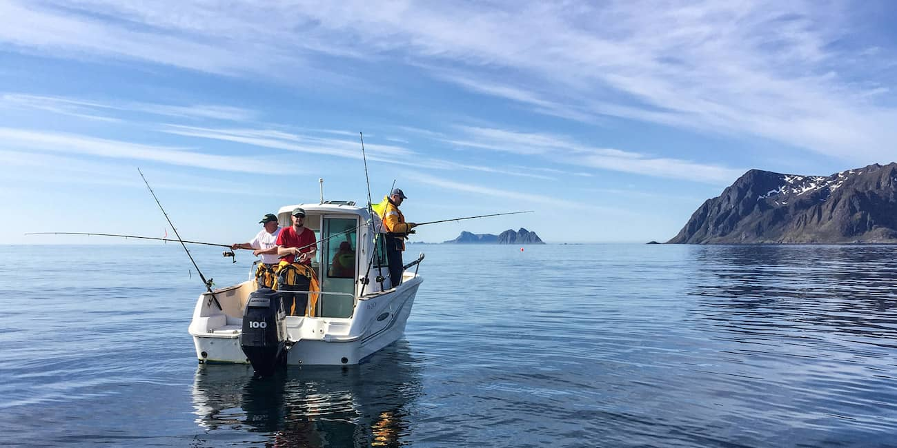Fishing boat in front of Lofoten. In the background the Maelstrom and the island Mosken